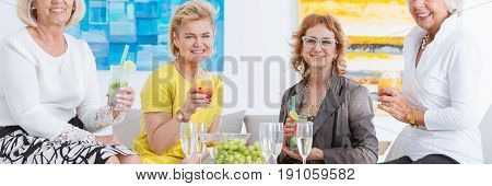 Senior female friends having drinks in art gallery and celebrating