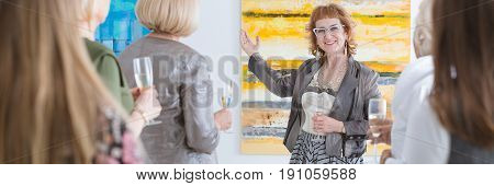 Senior elegant smiling woman presenting painting during art show