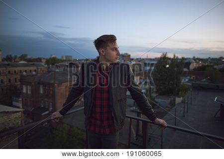 Young guy on roof at night. Youth, loneliness, new thoughts, free life, unusual people concept