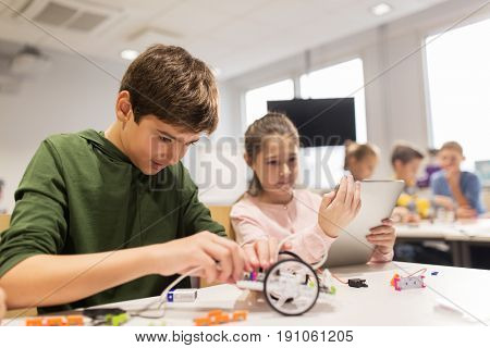 education, science, technology, children and people concept - group of happy kids or students with tablet pc computer programming electric toys and building robots at robotics school lesson