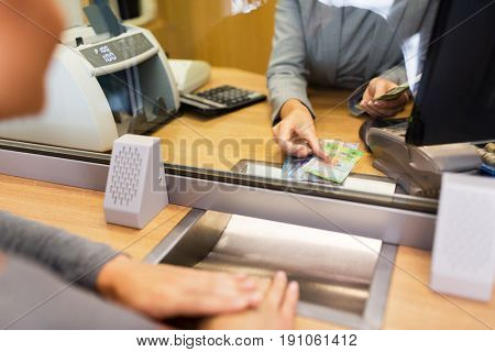 people, withdrawal, money, saving and finance concept - clerk counting swiss francs cash at bank office or currency exchanger