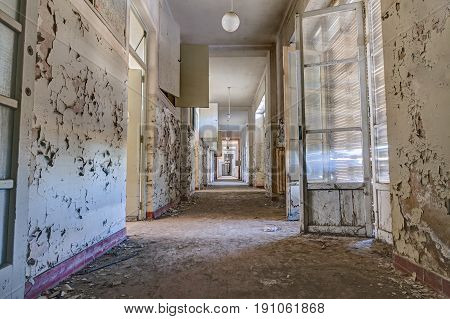 interior of an abandoned building with rubble and debris - desolate corridor of an old hospital