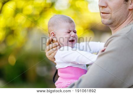 Close-up of tired young father with crying baby girl. Dad with daughter outdoors, love. Tiny child crying. Bonding, family, new life
