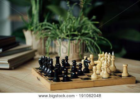 Chess Pieces Knights Standing Head To Head On Chessboard On The Table With Plants And Books