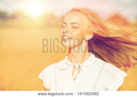 country, nature, summer holidays, vacation and people concept - happy smiling young woman or teenage girl in white enjoying sun on cereal field