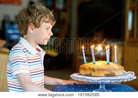 Adorable happy blond little kid boy celebrating his birthday. Child blowing candles on homemade baked cake, indoor. Birthday party for school children, family celebration of 6 years.