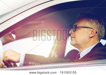 transport, business trip and people concept - happy senior businessman driving car