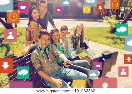 technology, education and people concept - group of happy teenage students or friends taking selfie by smartphone and monopod with menu icon