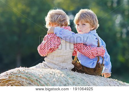 Two little kid boys, twins and siblings sitting on warm summer day on hay stack in wheat field. Happy children playing together. Best friends, family, happiness. Kids in traditional bavarian clothes