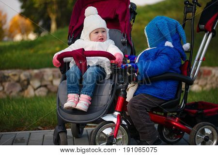 little boy and girl met in strollers