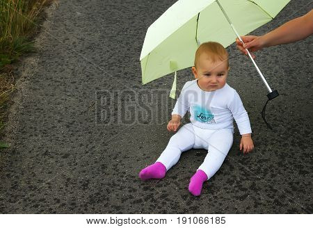 small baby is sitting on an asphalt road in the rain under an umbrella
