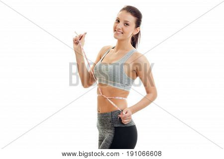 Cheerful brunette sports woman measure her waist and smiling on camera isolated on whtie background