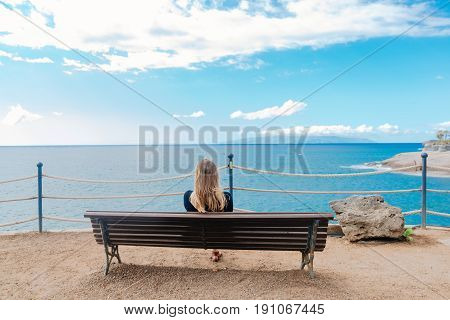 Woman Sitting Alone On The Wooden Bench In Front Of The Ocean