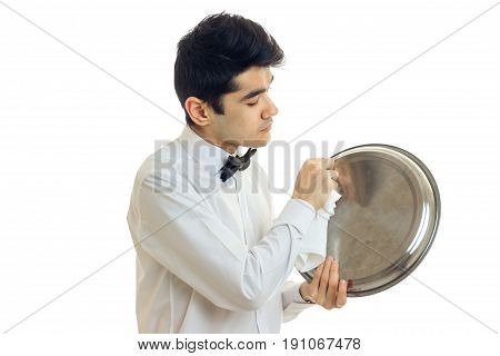 male waiter in uniform with bowtie cleans a trey isolated on white background