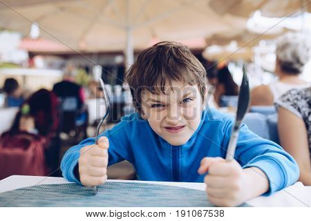 Hungry angry little boy waiting for his dinner at restaurant