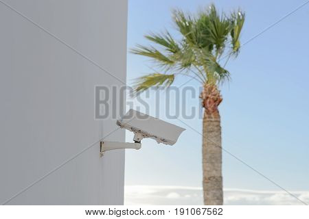 Old white security camera mounted on building wall in touristic resort