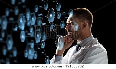 chemistry , science and people concept - male doctor or scientist in white coat looking at virtual projection of chemical formula over black background