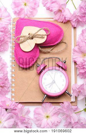 Alarm Clock And Pink Handmade Heart On Beige Notebook