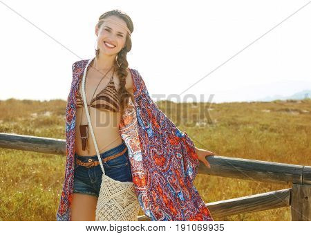 Smiling Trendy Boho Girl Outdoors In Summer Evening Near Fence