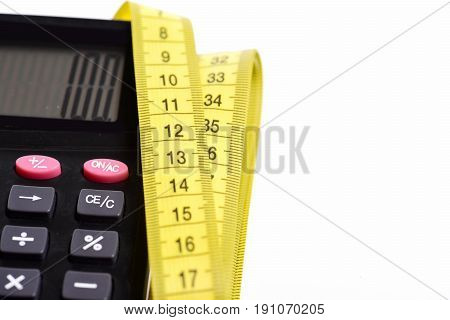 Calculator with number 100 with yellow measuring tape folded nearby isolated on white background. Concept of counting and size measurement