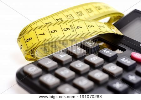 Calculator in black color and folded yellow tape measure isolated on white background as symbol of weight management diet and metering