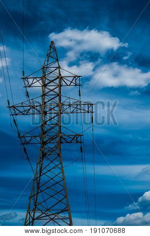 High voltage power line tower with blue sky on backgound