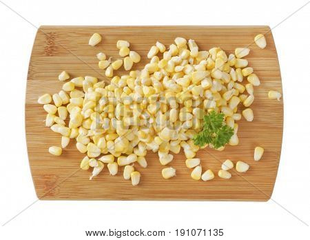 pile of sweet corn kernels on wooden cutting board