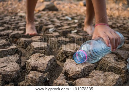Children pour water on the arid ground Drought concept.
