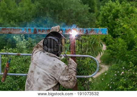 Welder at work. Welder cooks metal grate on the ground blowtorch on the ground in special clothes and mask welder.
