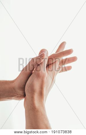 Close-up partial view of passionate young couple in love holding hands isolated on white