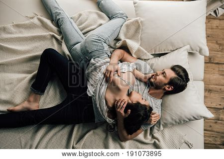 Top View Of Sensual Young Couple Of Lovers Lying And Hugging On Bed