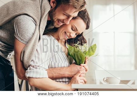 young smiling couple hugging and holding bouquet of flowers at home