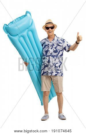 Full length portrait of a mature tourist with an air mattress making a thumb up gesture isolated on white background