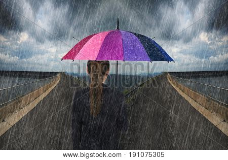 Business Woman Holding Umbrella With Falling Rain On Cross Road Spliting In Two Way