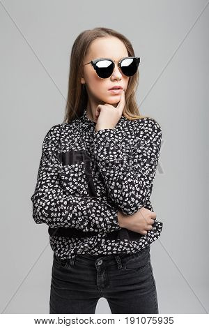 Portrait of young model girl with black sunglasses over gray background. woman dressed in black T-shirt, black jeans and white shoes