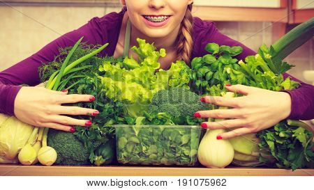 Smiling Woman In Kitchen With Green Vegetables