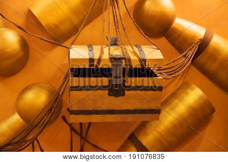 Wooden chest with an iron lock hanging on hemp ropes