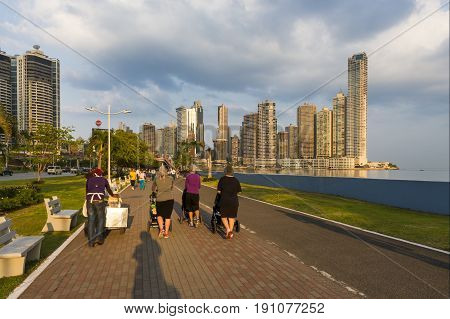Panama City Panama - March 18 2014: View of the downtown of the City of Panama with people walking in a promenade and modern buildings on the background.