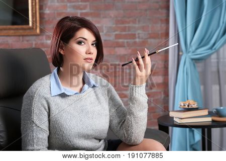 Young woman with cigarette holder at home