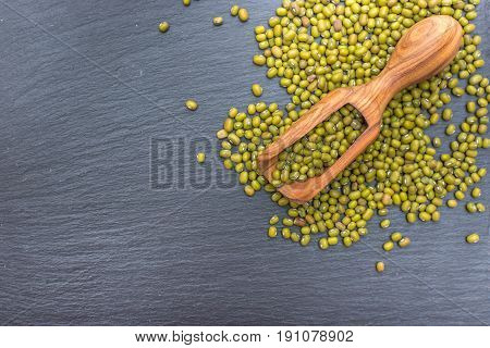 Green mung bean and olive wood scoop on black background of slate or stone. Top view