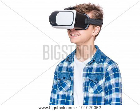 Happy teen boy wearing virtual reality goggles watching movies or playing video games, isolated on white. Cheerful teenager looking in VR glasses. Funny child experiencing 3D gadget technology.