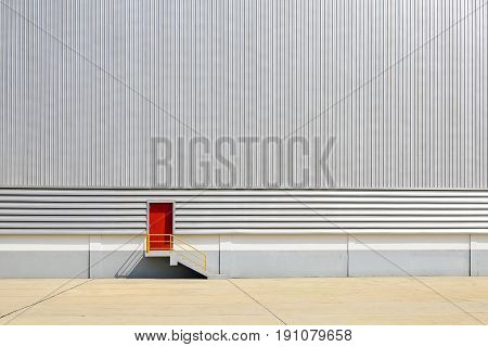 The red exit door at the sheet metal wall of factory building.