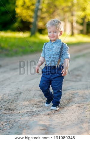 Portrait of toddler child outdoors. Rural scene with one year old baby boy