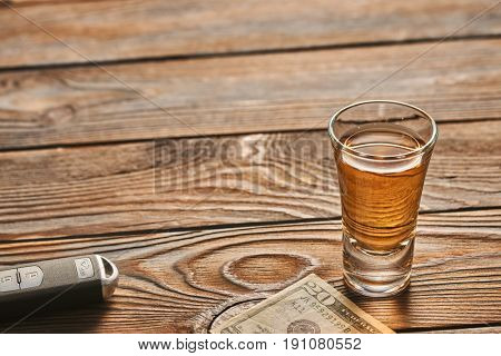 Glass of tequila or alcohol drink and car key on rustic wooden table with copy-space. Drink and drive and alcoholism concept. Safe and responsible driving concept.