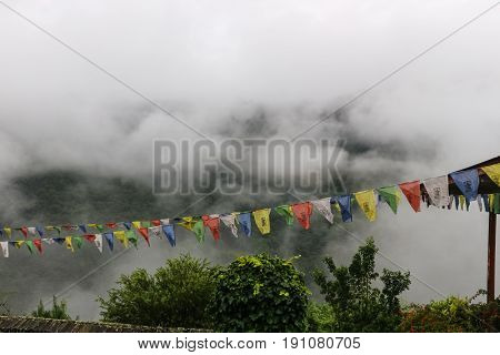 View Of Prayer Flags At Trongsa Dzong With Foggy Hills, Bumthang, Bhuta