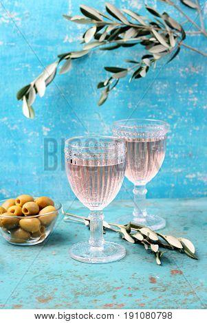 Glasses of wine on the aquamarine background and olives