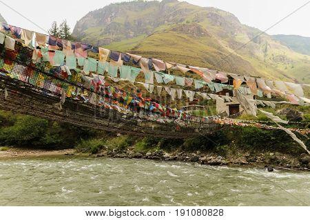 Prayer Flags On The Iron Bridge Of Tamchog Lhakhang Monastery, Paro River, Bhutan