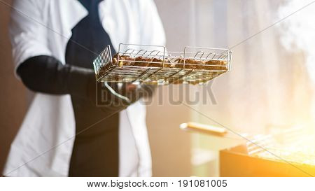 Cook in white robe and black gloves prepares meat on grill. Summer barbecue