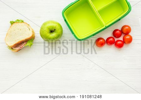 healthy break with apple, tomato and sandwich in green lunchbox on home wooden table background flat lay mock-up