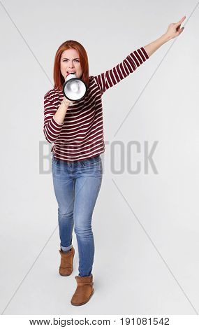 Protesting young woman shouting into megaphone on light background